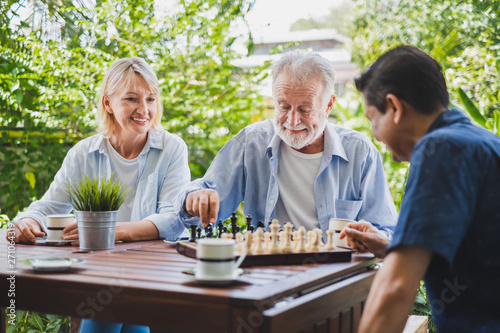 Fotomural Senior old man playing chess game on chess board for strategy and planning conce