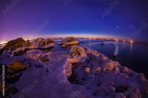 Foto auf Leinwand Violett On winter nights, snow and ice cover the rocks by the sea