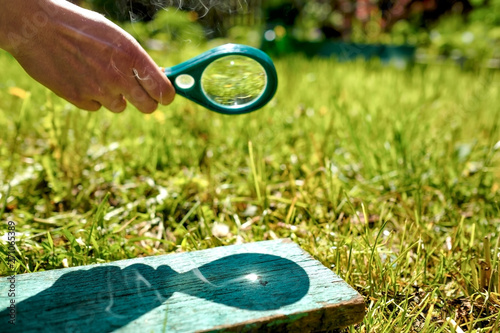Man holding a magnifying glass making fire, focused on wood on summer day Wallpaper Mural