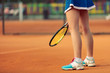 Beautiful female athlete with perfect body posing on tennis court, close up