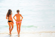 Rear view of two european girl in pink and black bikini walking on the beach in summer.