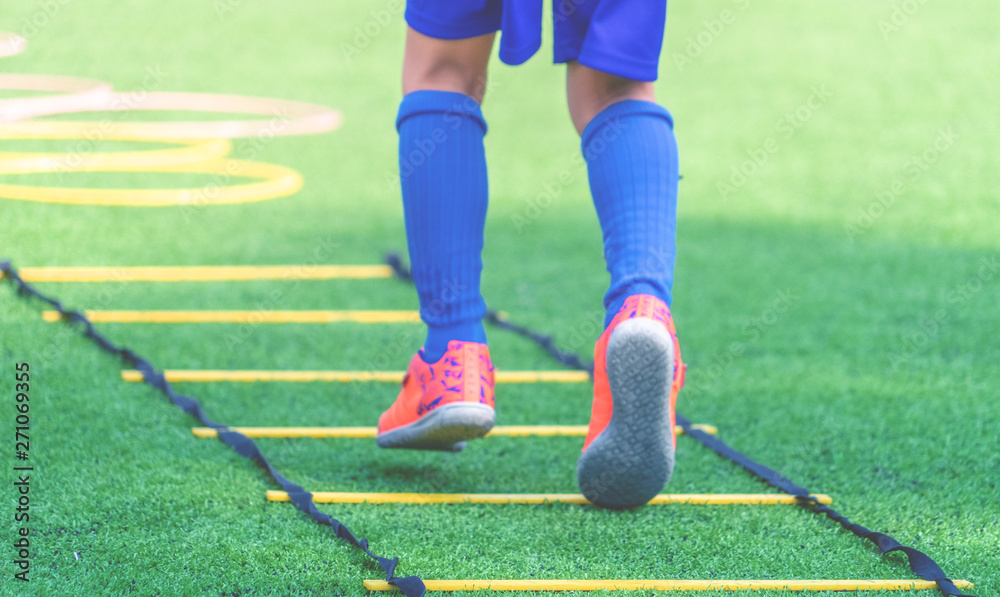 Fototapeta Child feet with soccer boots training on agility speed ladder in soccer training.