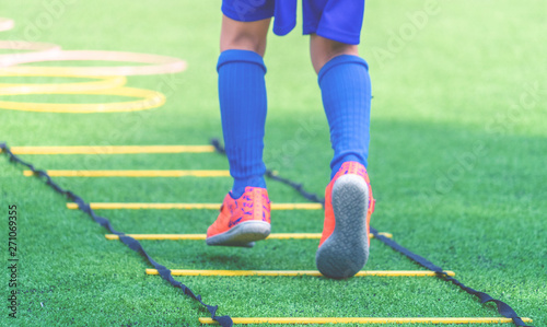 Child feet with soccer boots training on agility speed ladder in soccer training Canvas Print