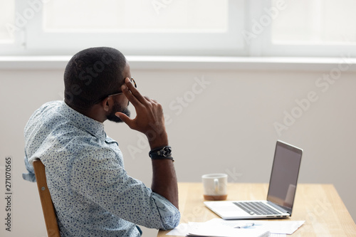 Thoughtful African American businessman looking out window sitting at office