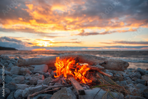 Foto op Canvas Grijs fire burns near the sea