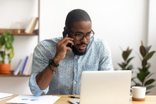 Serious African-american Employee Making Business Call Focused On Laptop Screen