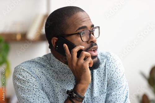 Close up african-american employee talking phone at workplace in office Tapéta, Fotótapéta
