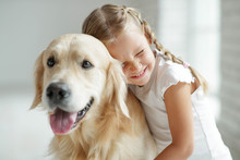A Child With A Dog At Home.