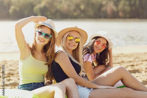 fototapeta na lodówkę Girlfriends playing on the beach in the summer.