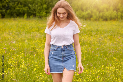 Valokuva  Ourdoor shot of young beautiful Caucasian girl in white t shirt and blue denim skirt posing against sunset in meadow, looking down, attractive female looking down