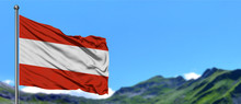 Austria Flag Waving In The Blue Sky With Green Fields At Mountain Peak Background. Nature Theme.