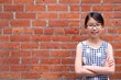 Portrait of young Asian girl teen wearing eyeglasses against red brick wall