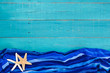 Blank teal blue wood sign with beach towel and starfish border
