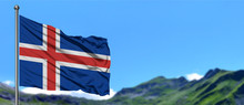 Iceland Flag Waving In The Blue Sky With Green Fields At Mountain Peak Background. Nature Theme.