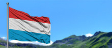 Luxembourg Flag Waving In The Blue Sky With Green Fields At Mountain Peak Background. Nature Theme.