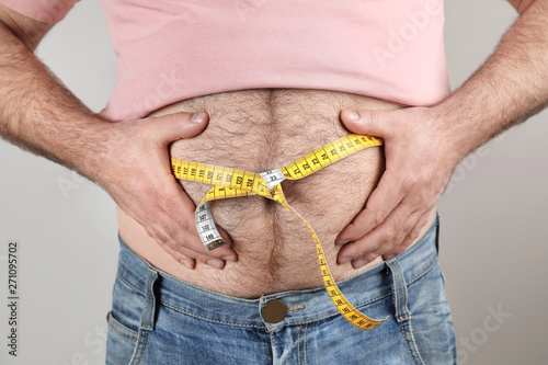 Overweight Man With Large Belly And Measuring Tape On Color