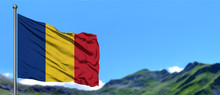 Romania Flag Waving In The Blue Sky With Green Fields At Mountain Peak Background. Nature Theme.