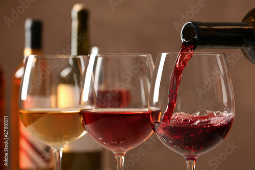 Pouring wine from bottle into glass on blurred background, closeup Fototapete