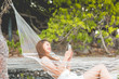 Summer Vacation of happy Asian woman wearing white bikini using mobile phone relax and lying in hammock on tropical island beach in Thailand,Travel in Thailand Destination,Summer vacations Concept