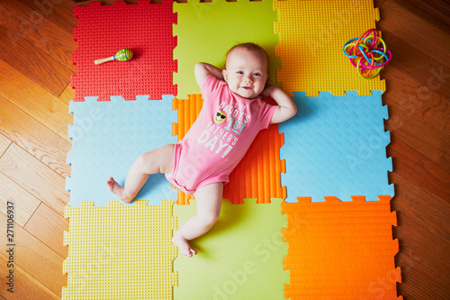 4 months old baby girl lying on colorful play mat Canvas Print