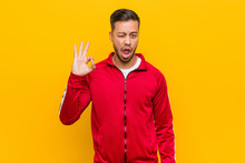 Young Filipino Fitness Man Winks An Eye And Holds An Okay Gesture With Hand.