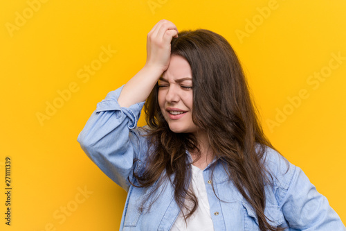 Valokuva  Young curvy plus size woman forgetting something, slapping forehead with palm and closing eyes