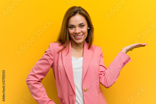 Valokuva  Young fashion business woman showing a copy space on a palm and holding another hand on waist