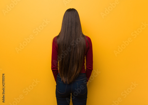Fotomural Intellectual young girl from behind, looking back