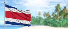 Waving Costa Rica Flag In The Sunny Blue Sky With Summer Beach Background. Vacation Theme, Holiday Concept.