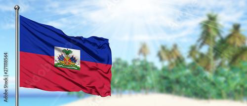 Fotografía Waving Haiti flag in the sunny blue sky with summer beach background