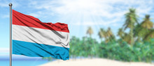 Waving Luxembourg Flag In The Sunny Blue Sky With Summer Beach Background. Vacation Theme, Holiday Concept.