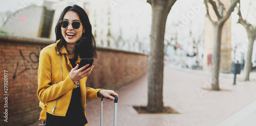 Fotografie, Obraz  Beautiful asian female with long dark hair wearing stylish yellow leather jacket and trendy sunglasses smiling at the camera while crossing the street with a suitcase on a bright spring day