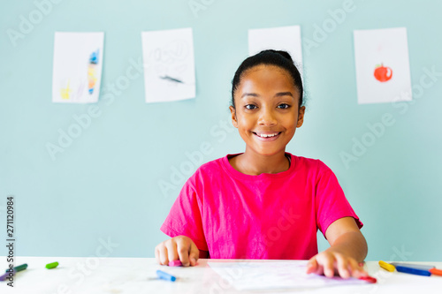 African American girl in T-shirt drawing with crayons while sitting at table against wall during art lesson at school, smiling and looking at camera Canvas-taulu