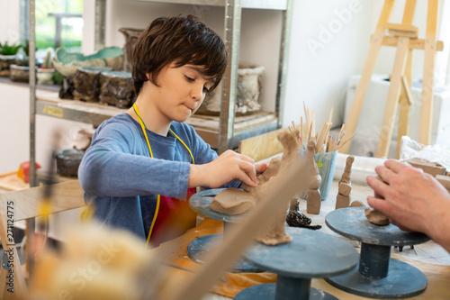 Poster Ecole de Danse Schoolboy feeling involved in sculpting clay animals