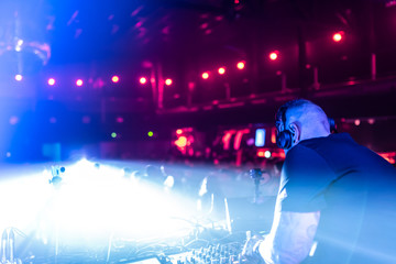 DJ Playing House and Techno Music in a Night Club. Mixing and Controlling the Music.
