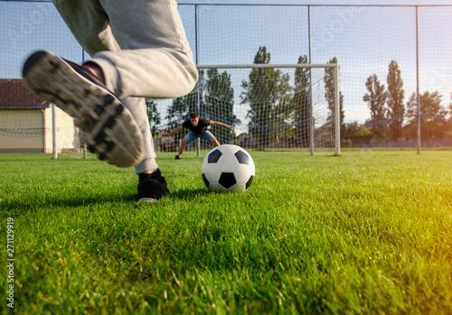 Obraz Closeup shot teen preparing to kick the ball , penalty shootout concept  - fototapety do salonu