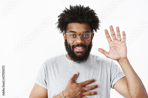 Valokuvatapetti Friendly nice african american man at meeting holding palm on chest and raising