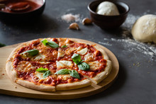 Ingredients For Traditional Italian Pizza Margherita With Tomato Sauce, Mozzarella Cheese, Basil On A Dark Concrete Background. Pizza Recipe And Menu.