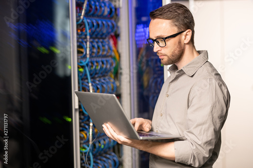 Leinwand Poster Serious thoughtful handsome young server engineer in glasses standing in databas