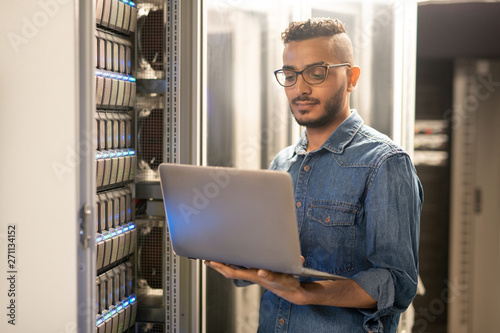 Leinwand Poster Serious skilled young Arabian IT specialist with beard standing by modern server