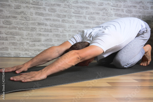 Fotografia  Man exercising stretching back yoga pose on the  mat.