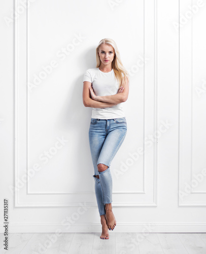 Fotobehang Artist KB Young blond woman leaning on a decorative wall