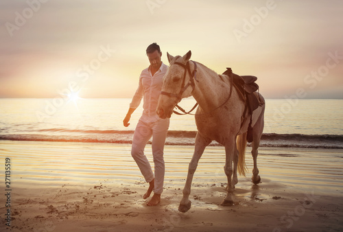Photo sur Toile Artiste KB Handsome, young man walking with a stallion alongside the coast
