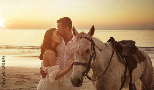 Photo sur Toile Artiste KB Young couple walking a majestic horse - seaside landscape