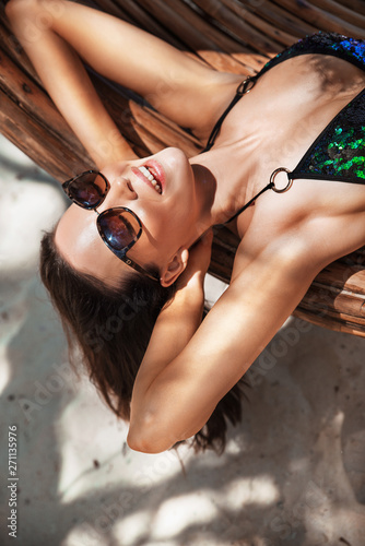 Photo sur Toile Artiste KB Sensual brunette lady relaxing on a bamboo circle - swing