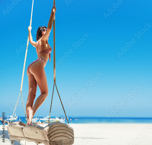 Photo sur Toile Artiste KB Sensual brunette lady relaxing on a bamboo see-saw