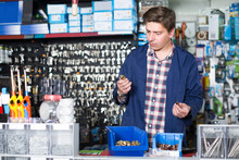 Man Standing Near The Counter And Selling Details For Plumbing In Hardware Shop