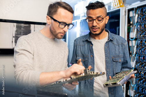 Fotografía  Concentrated smart young database engineers in glasses viewing circuit boards of
