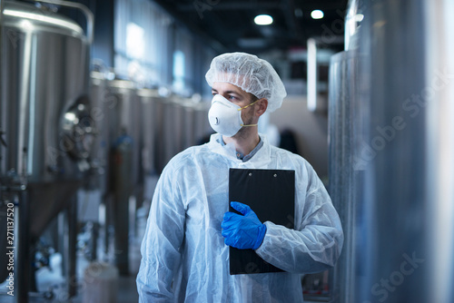 Fotografía  Technologist in protective white suit with hairnet and mask standing in food factory