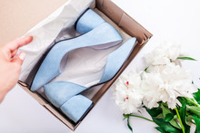Female Blue Wedding Shoes In Box With Flowers On White Background. Woman Opens Box